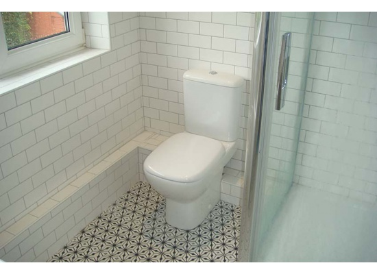 tiled bathroom with toilet unit installed